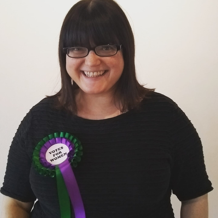 Chella Quint wearing a 'Votes for Women' rosette.